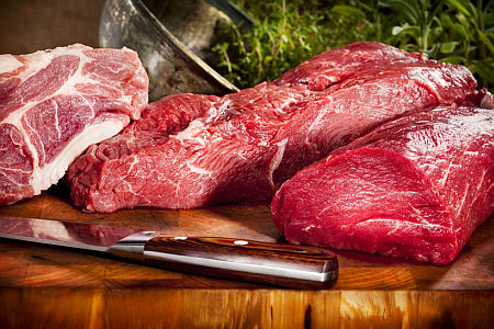 Raw meat selection on wooden cutting board with knife