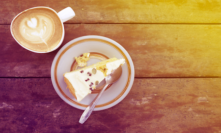 Slice of homemade pumpkin cake with cup of latte on wooden table in warm sun light